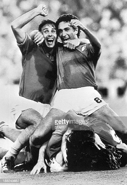 Italian defenders Antonio Cabrini and Claudio Gentile celebrate over their fallen teammates after forward Alessandro Altobelli scored the third goal...