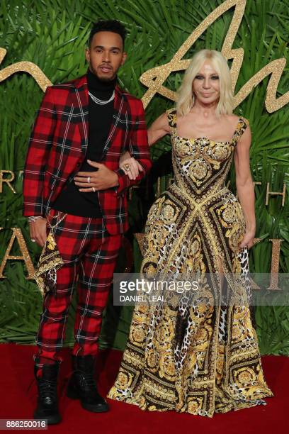 Italian designer Donatella Versace who won the fashion icon award poses with Formula One driver Lewis Hamilton on the red carpet upon arrival to...