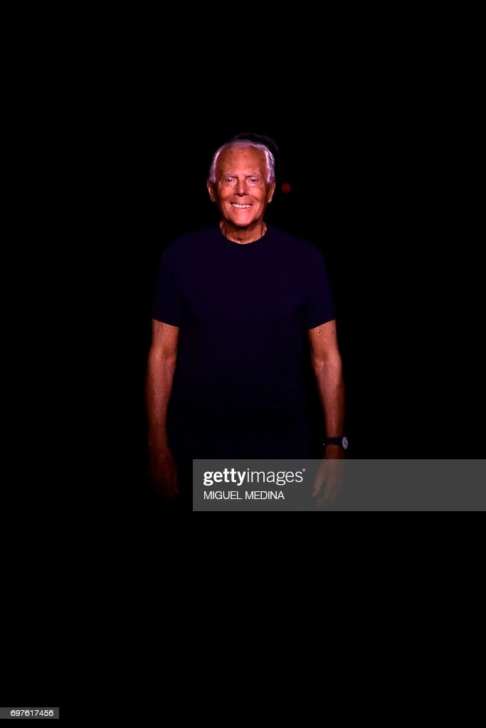 Italian designer Giorgio Armani greets the audience at the end of the show during the Men's Spring/Summer 2018 fashion shows in Milan, on June 19, 2017. / AFP PHOTO / Miguel MEDINA