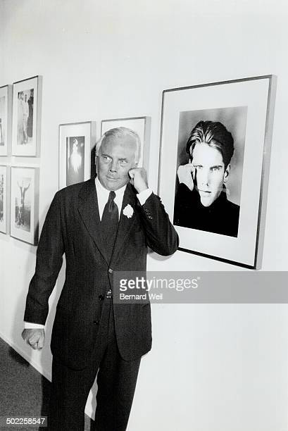 Italian Designer. Giorgio Armani, right mimics a photofrom his fall/winter '87 collection, part of the retrospective at the Fashion Institute of...