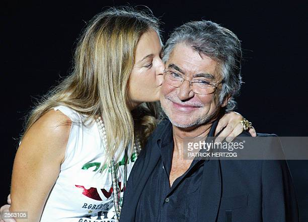 Italian designer Roberto Cavalli is kissed by his wife Eva as the audience aplauds after the presentation of his collection, 04 October 2003, during...
