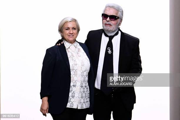 Italian designer Silvia Venturini Fendi and German fashion designer Karl Lagerfeld acknowledge the audience at the end of the Fendi Couture's...