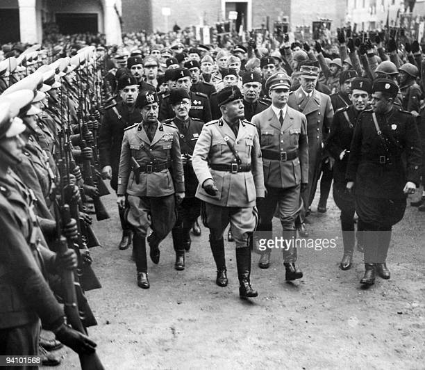 Italian dictator and Prime minister Benito Mussolini known as il Duce reviews troops 29 October 1937 in Rome followed by Rudolf Hess Adolf Hitler's...