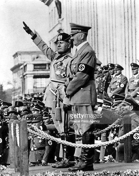 Italian dictator Benito Mussolini saluting next to German dictator Adolf Hitler outside the Temple of Heroes during a parade in Munich