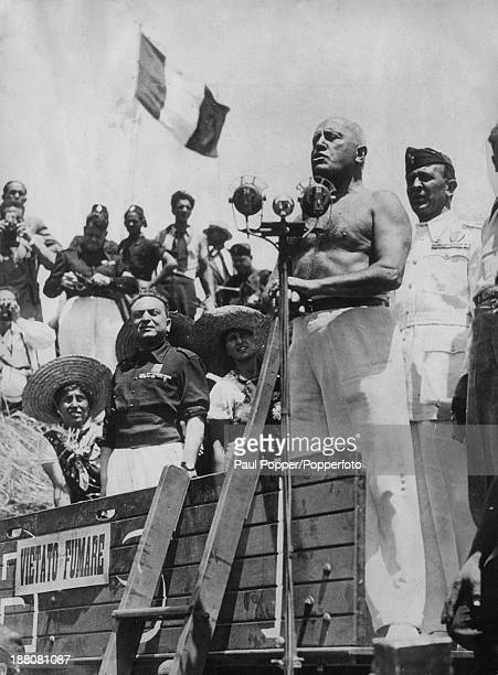 Italian dictator Benito Mussolini stripped to the waist and standing on the platform of a threshing machine as he gives a speech to inaugurate the...