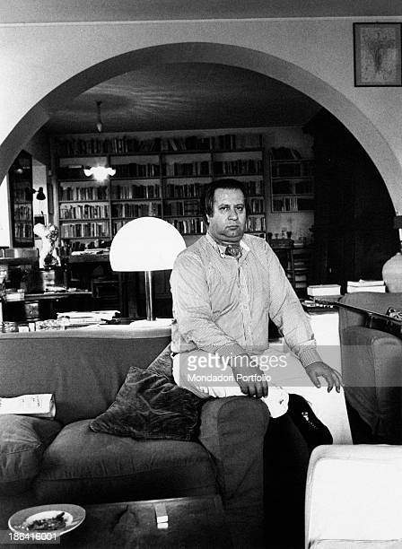 Italian director and playwright Tinto Brass sitting on the arm of a couch in his country house Rome 1979