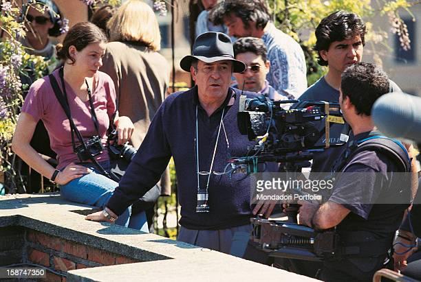 Italian director and scenarist Bernardo Bertolucci talking on the set of the film Besieged Rome 1998