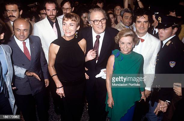 Italian director and scenarist Federico Fellini smiling in the crowd beside his wife Italian actress Giulietta Masina and British acrtess Barbara...