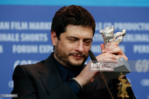 TOPSHOT Italian director and screenwriter Claudio Giovannesi poses with the Silver Bear for best screenplay for the film Piranhas during a press...