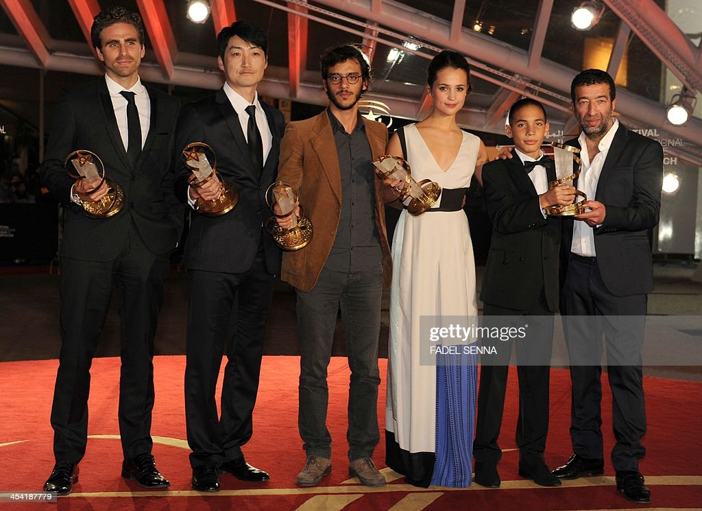 Italian director Andre Pallaoro poses with his 'best director prize' next to South Korean director Lee Su-Jin with the 'Golden Star award', Cuban filmmaker Carlos Machado Quintella with the 'Jury award', Swedish actress Alicia Vikander with 'the best performance by an actress prize', French-Moroccan actors Didier Michon and Slimane Dazi with 'the best performance by an actor prize' during the closing ceremony of the 13th Marrakech International Film Festival on December 7, 2013 in Marrakech.