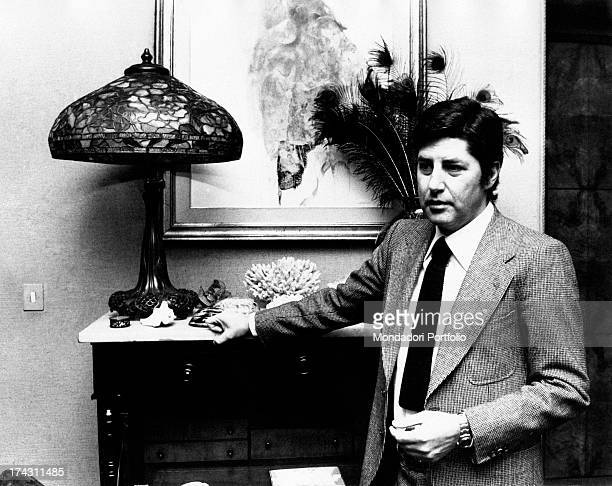 Italian director Antonello Falqui posing keeping a hand on a piece of furniture. Rome, 1970s.