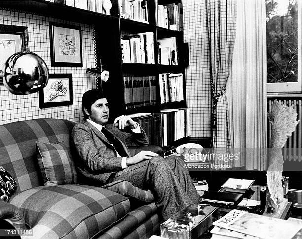 Italian director Antonello Falqui sitting on a sofa. Rome, 1970s.