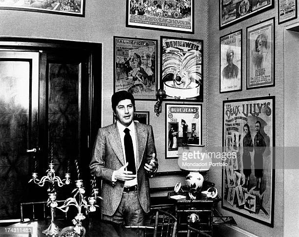 Italian director Antonello Falqui smiling. On the walls of the flat, many posters. Rome, 1970s.