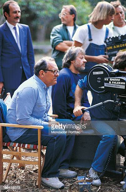 Italian director Damiano Damiani sitting behind a cameraman on the set of the film Pizza connection 1984