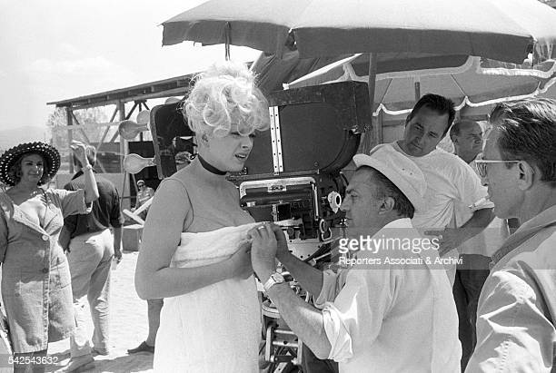 Italian director Federico Fellini adjusting a towel around Italian actress Sandra Milo on the set of Juliet of the Spirits 1965