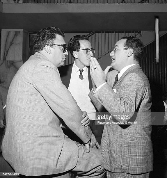 Italian director Federico Fellini and Italian producer Dino De Laurentiis talking at the airport before leaving 1956