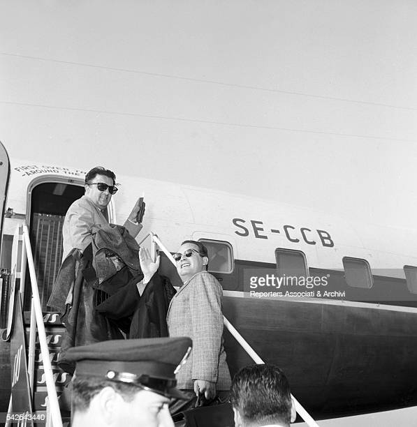 Italian director Federico Fellini and Italian producer Dino De Laurentiis with his children Federico and Veronica walking at the airport 1956
