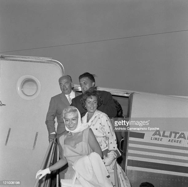 Italian director Federico Fellini getting down an Alitalia airplane with his wife Giulietta Masina and the romanian actress Nadia Gray 1960s