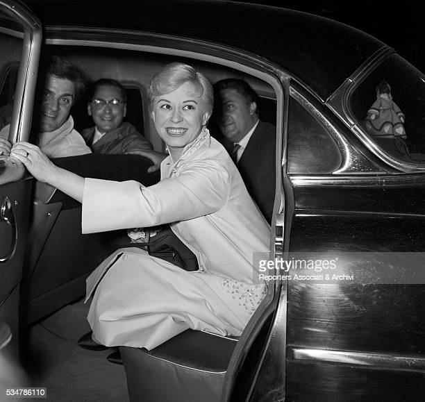 Italian director Federico Fellini his brother Riccardo and Italian actress Giulietta Masina on a car at the premiere of the film Juliet of the...