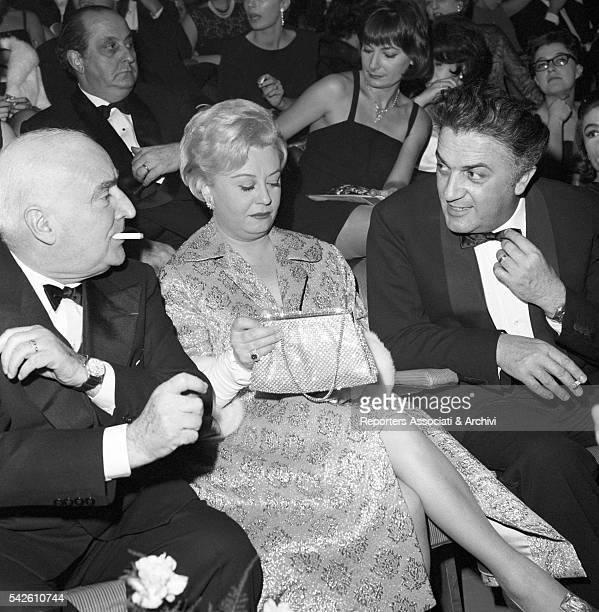 Italian director Federico Fellini his wife Italian actress Giulietta Masina and Italian publisher Angelo Rizzoli in cinema Fiamma at the premiere of...