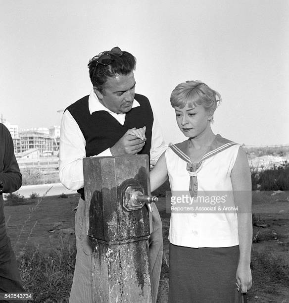 Italian director Federico Fellini holding hands with Italian actress Giulietta Masina on the set of Nights of Cabiria 1957
