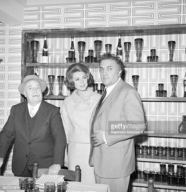 Italian director Federico Fellini Italian actress Sylva Koscina and Italian publisher Angelo Rizzoli in a restaurant Rome 1965