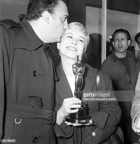 Italian director Federico Fellini kissing Italian actress Giulietta Masina at Ciampino Airport after they won the Academy Award for the film Nights...