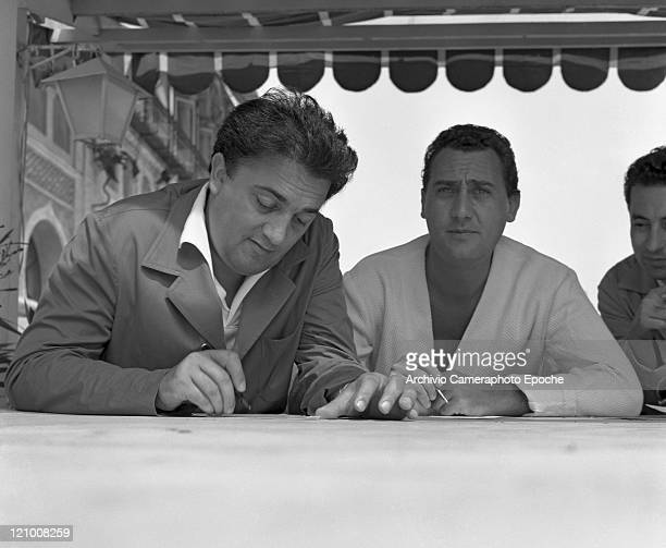 Italian director Federico Fellini portrayed while signing autographs with the italian actor Alberto Sordi in Lido Venice for presenting the movie 'I...