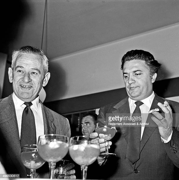 Italian director Federico Fellini toasting with a glass of champagne with American director William Wyler at the cocktail party for the beginning of...