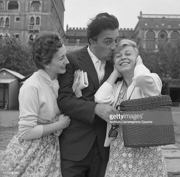 Italian director Federico Fellini wearing a suit and holding sunglasses portrayed among the actress Valentina Cortese and his wife Giulietta Masina...