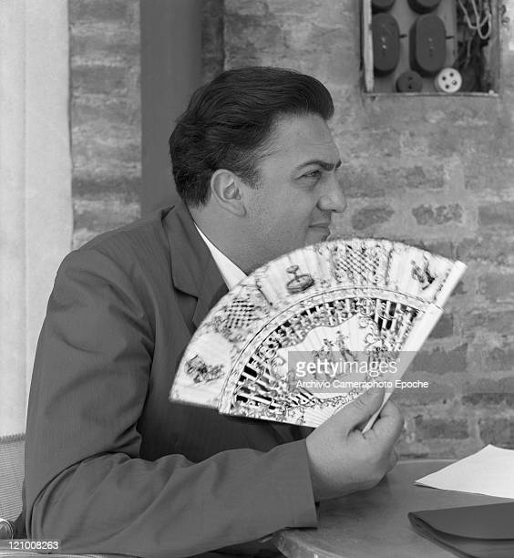 Italian director Federico Fellini wearing a suit portrayed while holding a fan Venice 1954
