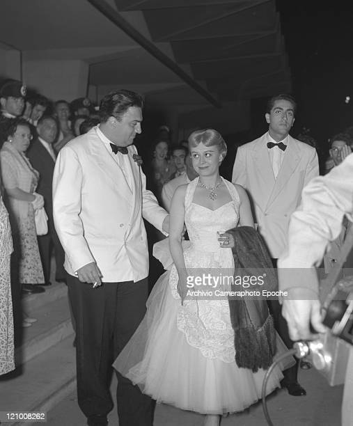 Italian director Federico Fellini wearing a tuxedo and a bow tie and smoking a cigarette and his wife Giulietta Masina wearing an evening dress and...