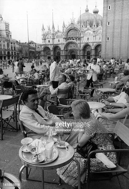 Italian director Federico Fellini with his wife actress Giulietta Masina sitting at the table in front of a bar in St Mark's Square Venice August 1955