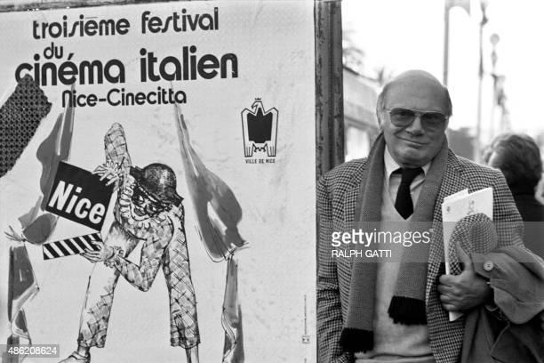 Italian director Francesco Rossi poses near the cinema poster of the 3rd Italian Film Festival, on December 5, 1981 in Nice.