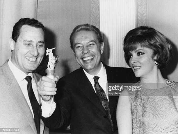 Italian director Gian Luigi Rondi holding his 'A Borselli' prize with actors Alberto Sordi and Gina Lollobrigida, Rome, April 1967.