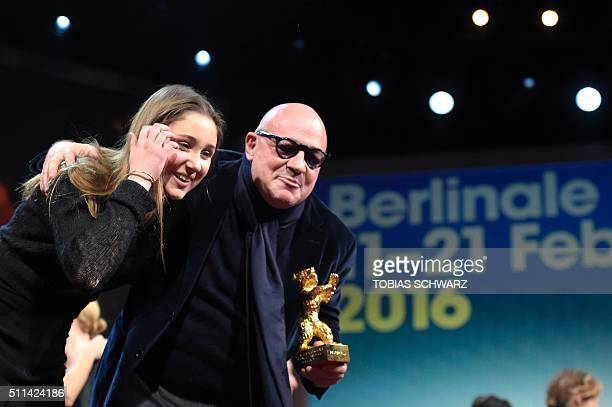 """Italian director Gianfranco Rosi poses with his daughter after receiving the Golden Bear for Best Film for the film """"Fuocoammare """" during the awards..."""