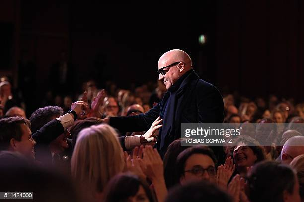 """Italian director Gianfranco Rosi reacts on his way to the stage to receive the Golden Bear for Best Film for the film """"Fuocoammare """" during the..."""