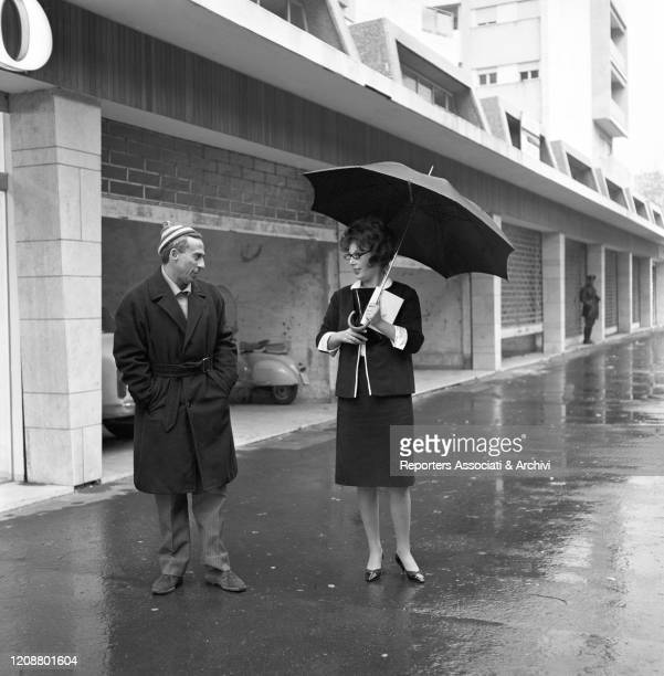 Italian director Gianni Puccini talking to Italian actress Daniela Rocca standing under the rain with an umbrella during the shooting on the set of...