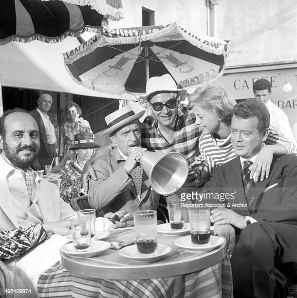 Italian director Giuseppe Lipartiti Italian actress Alessandra Panaro Italian actor and comedian Nino Taranto sitting around a table on the set of...