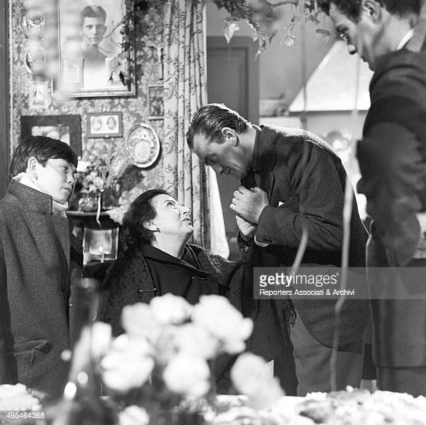 Italian director Luchino Visconti holding by her hand Greek actress Katina Paxinou on the set of the film Rocco and His Brothers Italian actor Rocco...