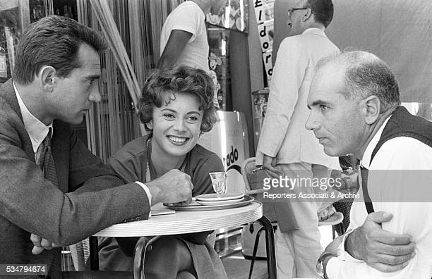 Italian director Luigi Comencini and Italian actorsi Walter Chiari and Anna Maria Ferrero sitting at the table in a café on the set of the film...