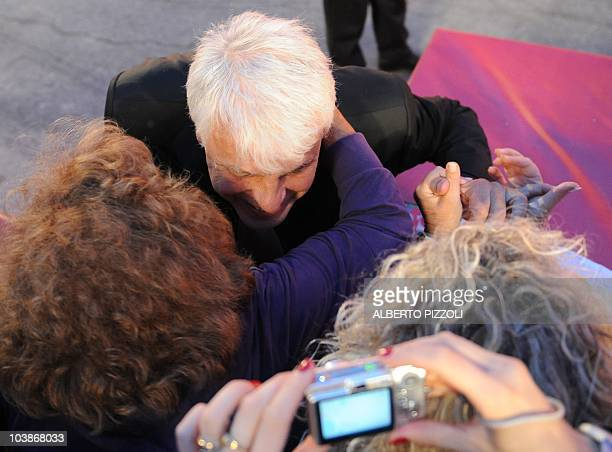 Italian director Michele Placido is hugged by a fan as he arrives for the screening of 'Vallanzasca gli angeli del male' at the 67th Venice Film...