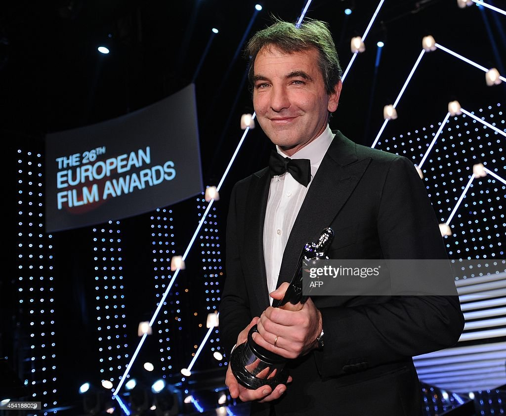 Italian director Paolo Sorrentino poses for a photo with his award on stage at the 26th European Film Awards ceremony on December 7, 2013 in Berlin. Every year, the various activities of the European Film Academy culminate in the ceremony of the European Film Awards. In a total of 21 categories, among them European Film, European Director, European Actress and European Actor, the European Film Awards annually honour the greatest achievements in European cinema.