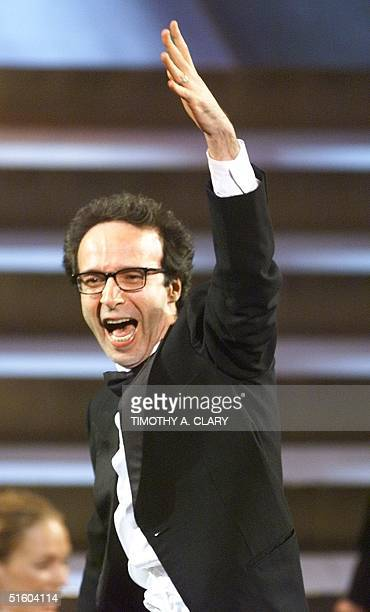 Italian director Roberto Benigni stands in his chair and celebrates after winning an Oscar for Best Foreign Language Film for his movie Life is...