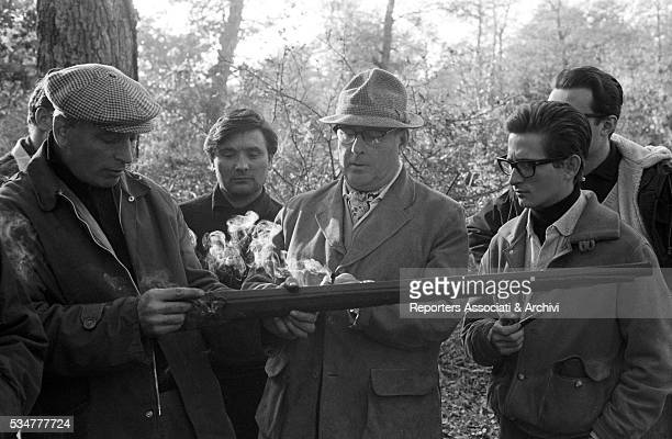 Italian director Roberto Rossellini and his son Renzo directing the documentary The Iron Age watching how a rifle works on the set 1965