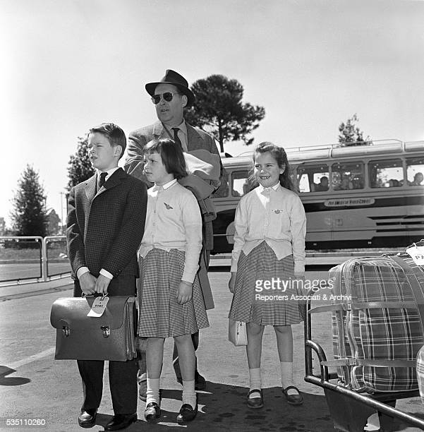 Italian director Roberto Rossellini posing with his children Robertino, Isotta and Isabella at the airport. Italy, 14th April 1960