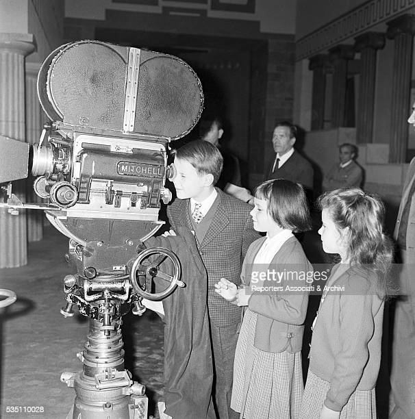 Italian director Roberto Rossellini showing a movie camera to his children Robertino Isotta and Isabella Italy 1957