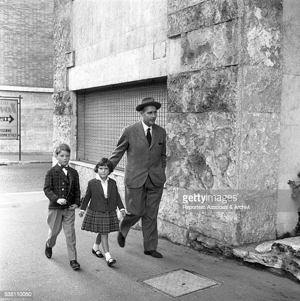 Italian director Roberto Rossellini walking with his children Robertino and Isotta Italy 1957