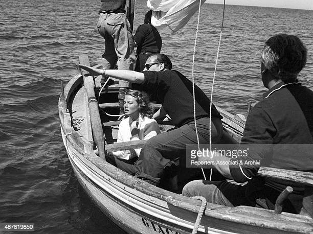 Italian director scriptwriter and film producer Roberto Rossellini illustrating a scene to Swedish actress Ingrid Bergman on a rowing boat on the set...