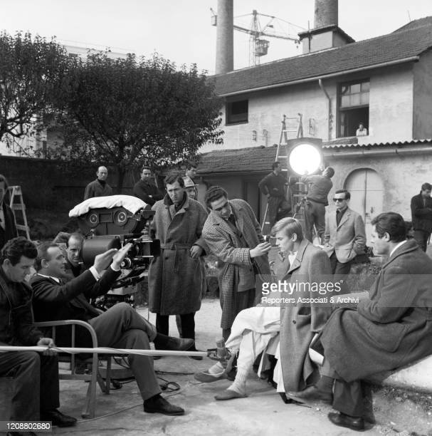 Italian director Valerio Zurlini sitting among other people and chatting with Italian actor Marcello Mastroianni and French actor Jacques Perrin...